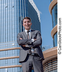 smiling business man standing in front of the business center.