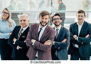smiling business man standing in front of the business team