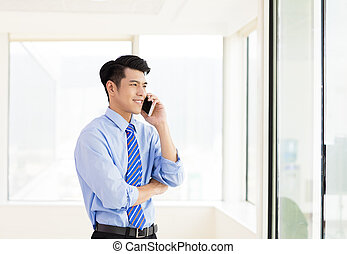 smiling business man talking on the phone in  office