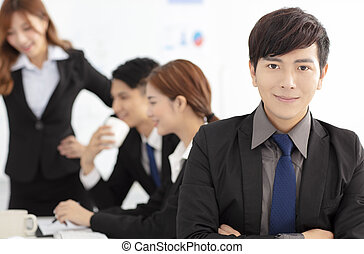 smiling business man with colleagues on background