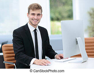 Smiling business man working on computer in a modern office