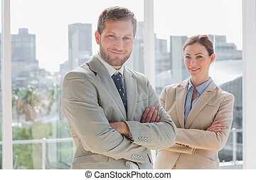 Smiling business partners with arms crossed in bright office