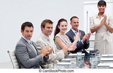 Smiling business people applauding a colleague after ...