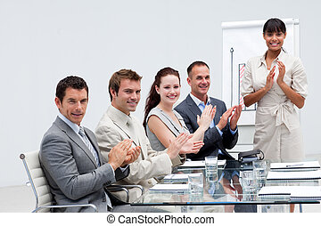 Smiling business people applauding a colleague after giving a presentation