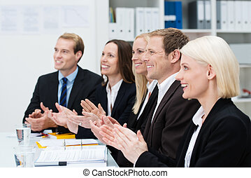 Smiling business people clapping their hands at the end of a...