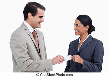 Smiling business people exchanging business cards against a...