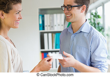 Smiling business people exchanging visiting card