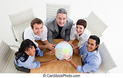 Smiling business people holding a globe in a meeting