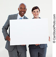 Smiling business people holding white card against white...