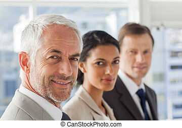 Smiling business people looking in the same way in their ...