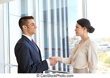 smiling business people shaking hands at office