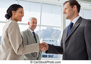 Smiling business people shaking hands with smiling colleague