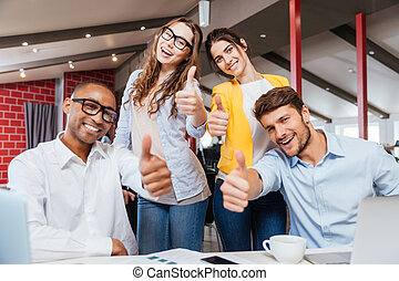 Smiling business people showing thumbs up working in office