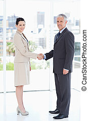 Smiling business people standing upright while warmly shaking hands