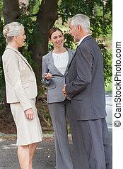 Smiling business people talking together