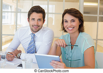 Smiling business people with digital tablet in office