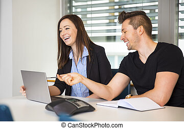 Smiling Business People With Laptop Communicating At Desk