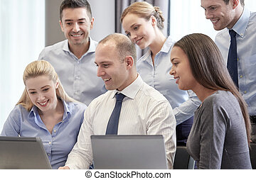smiling business people with laptop computer