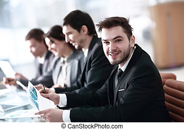 Smiling business people with paper work in board room
