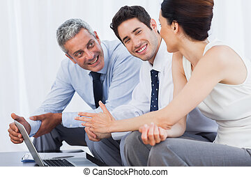Smiling business people working with their laptop on sofa