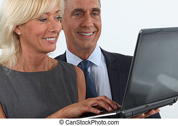 Smiling business professionals looking at a laptop