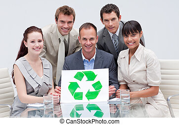 Smiling business team holding a recycling symbol in the office. Ecological business