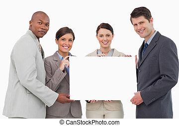 Smiling business team holding blank sign together