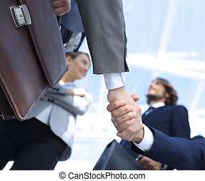 team looking at a business handshake partner.
