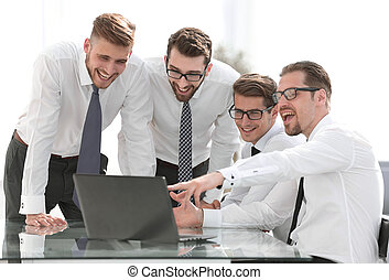 smiling business team looking at the laptop screen