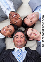 Smiling business team lying on the floor with heads together