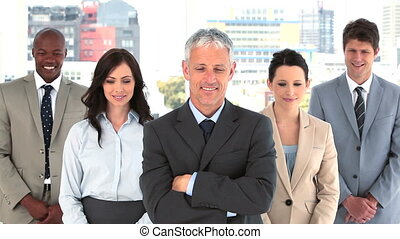 Smiling business team standing together with arms crossed in...