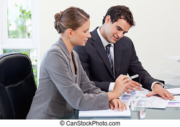 Smiling business team studying statistics