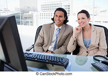 Smiling business team using a computer