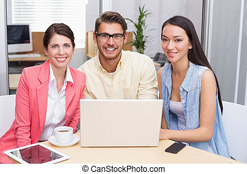 Smiling business team using laptop and having coffee