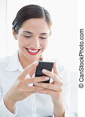 Smiling business woman looking at mobile phone