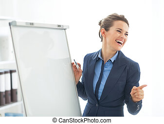 Smiling business woman near flipchart pointing