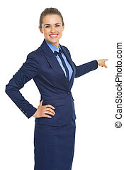 Smiling business woman pointing back on copy space
