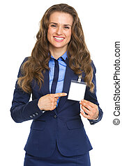 Smiling business woman pointing on badge