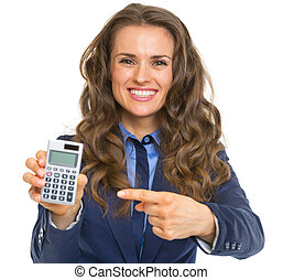 Smiling business woman pointing on calculator