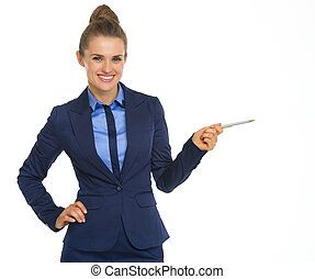 Smiling business woman pointing on copy space with pen