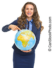 Smiling business woman pointing on globe