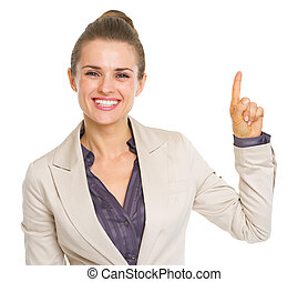 Smiling business woman pointing up on copy space