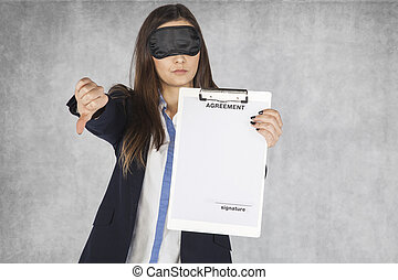 Smiling business woman shows thumb upwards, blindfolded