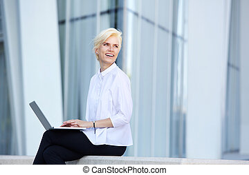 Smiling business woman sitting outside with laptop.