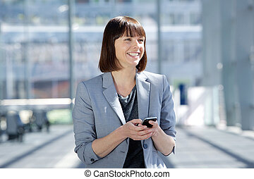 Smiling business woman walking with cell phone