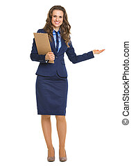 Smiling business woman with clipboard pointing on copy space
