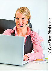 Smiling business woman with headset working on laptop