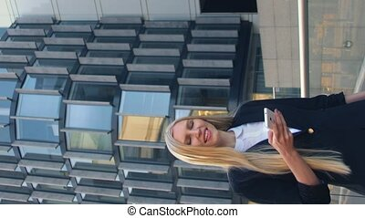 Modern blond woman in elegant outfit holding phone and standing on street with modern architectural buildings. Video with Vertical Screen Orientation 9:16