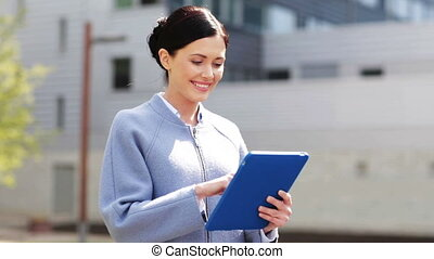 smiling business woman with tablet pc in city