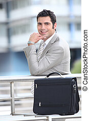 Smiling businessman and briefcase
